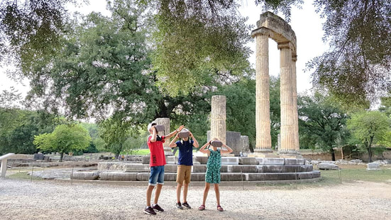 kids having fun with virtual reality glasses and an audio guide at the archaeological site of Olympia Greece